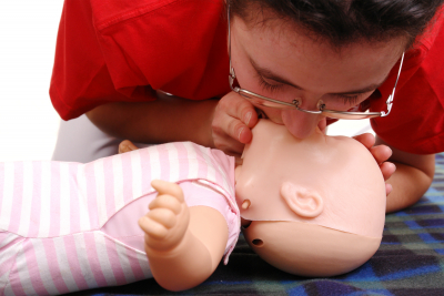 lady performing a CPR on a child dummy